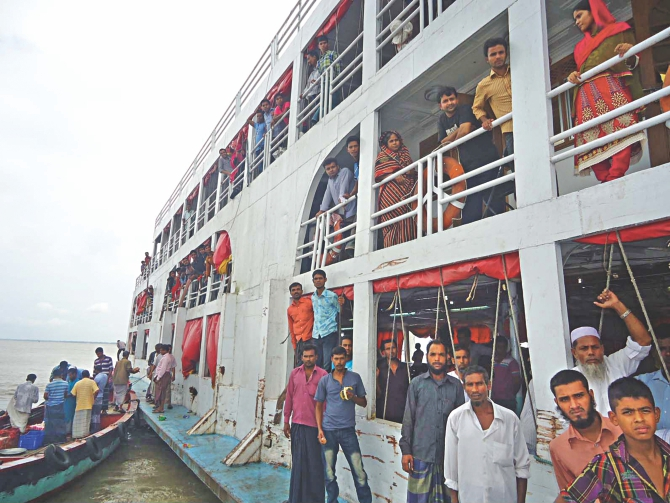 MV Sattar Khan-1 stuck in a char in the middle of the Meghna near Chandpur. The vessel started its journey to Patuakhali from Dhaka on Friday evening but got stranded there later that night. The passengers are seen being rescued yesterday afternoon. Photo: Star