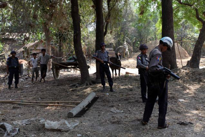 Myanmar policemen stand guard to provide security as they patrol in a village in Okpo township, Bago Region, about 120 miles from Yangon in Myanmar on March.28, 2013. Photo: AP