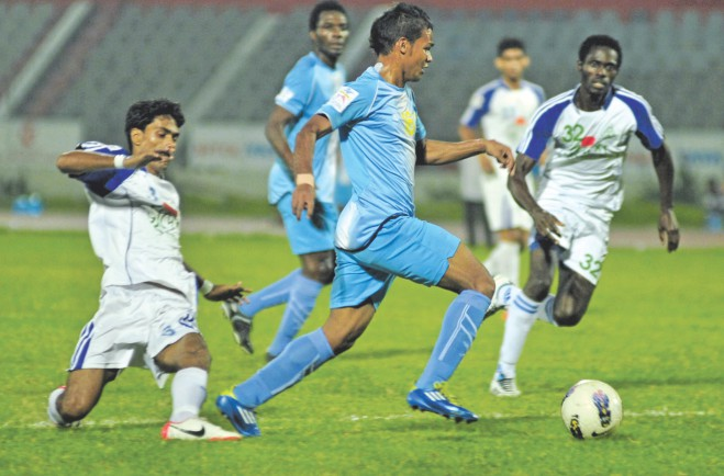 Abahani right-back Nasirul Islam (C) skips past Uttar Baridhara defenders during their 5-2 victory in the Nitol Tata Bangladesh Premier League match at the Bangabandhu National Stadium yesterday. PHOTO: STAR