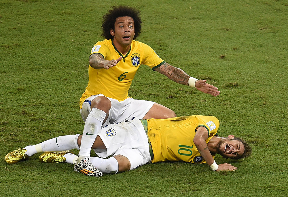 Neymar of Brazil lies injured while Marcelo of Brazil appeals during the 2014 FIFA World Cup Brazil Quarter Final match WITH Colombia. Photo: Getty Images