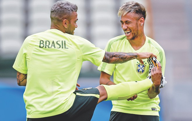 Though Brazil's place in the round of 16 is not confirmed as yet, their stars Neymar (R) and Dani Alves appeared relaxed in their training session in Fortaleza. PHOTO: GETTY IMAGES