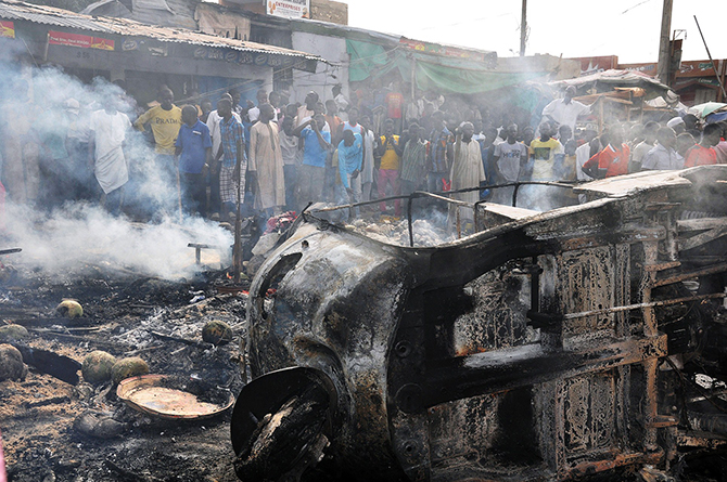 People gather to look at a burnt vehicle following a bomb explosion that rocked the busiest roundabout near the crowded Monday Market in Maiduguri, Borno State, on July 1, 2014. Photo: Getty Images
