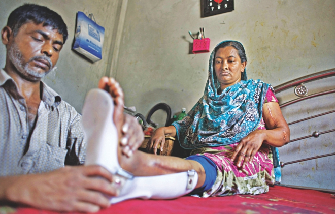 Hasu attaches an ankle-foot orthosis to the left leg of his wife Feli, one of the workers pulled out alive from the rubble of Rana Plaza last year. With a paralysing feeling in her left leg and inability to bend her left arm, she is almost immobile and completely dependent on her husband. Hasu had to quit his job as a caretaker of a house nearby to take care of the family. The photo was taken yesterday.  Photo: Rashed Shumon