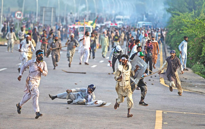 Anti-government protesters run after police personnel and beat a riot policeman, while one of them returns a tear gas shell towards law enforcers in Islamabad yesterday. Photo: Reuters/AFP