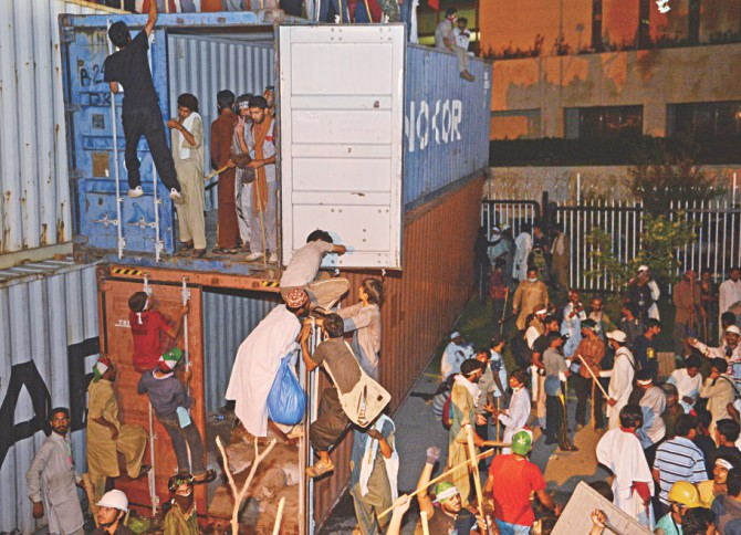 Protesters try to climb containers which were used to block the way of PM's house during the clashes. Photo: AFP