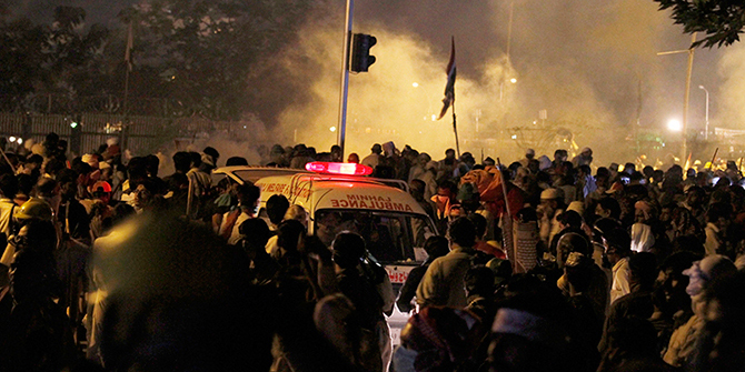 An ambulance carrying injured people makes way through protestors running for cover following police firing tear gas during clashes near prime minister's home in Islamabad, Pakistan, Saturday, August 30. Photo: APAP