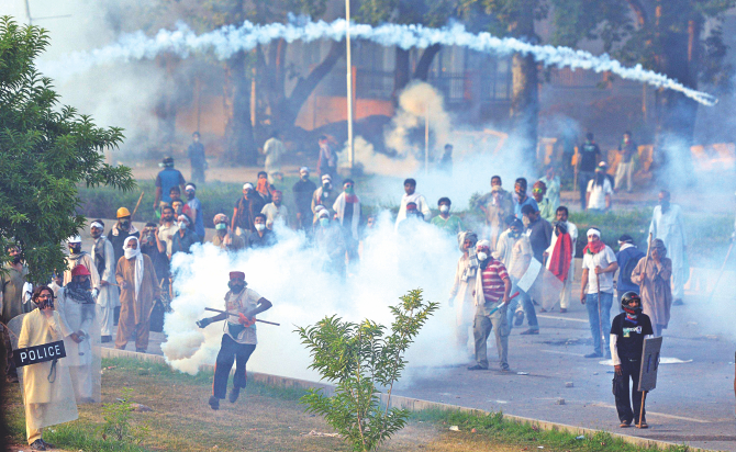 One of the supporters of Canadian cleric Tahir ul Qadri returns a teargas shell towards police during clashes near the Pakistan prime minister's residence in Islamabad yesterday.   Photo: AFP