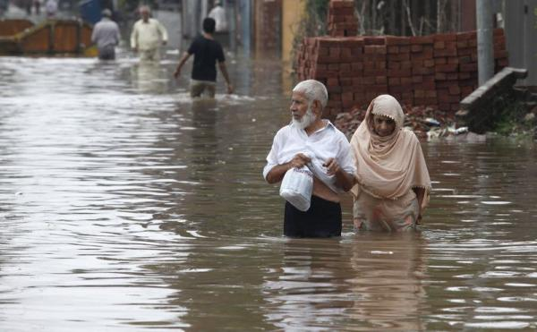 A couple wades through a flooded road after heavy rains in Lahore September 4, 2014. Photo: Reuters