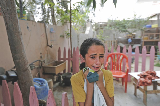 A girl mourns the death of a relative; and medics evacuate an injured man from Shejaiya district, yesterday. Photo: AFP