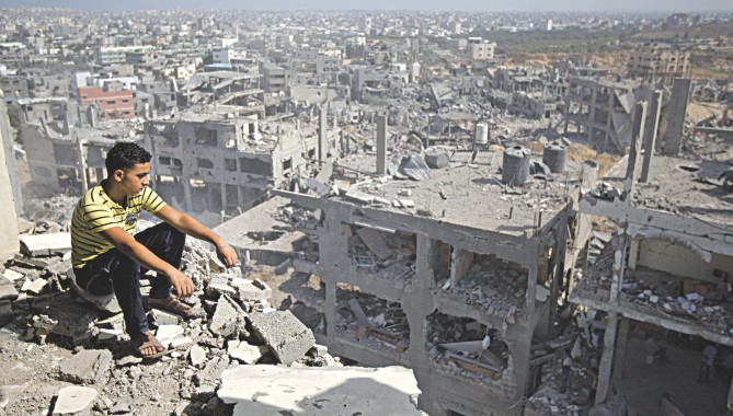 A Palestinian man looks at the rubble of his neighbourhood in Gaza after Israeli air strike destroy the area. File photo