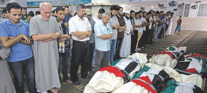 Palestinian mourners pray over five bodies, all from the Halaq family, during their funeral in the Jabalia refugee camp, in the Gaza Strip, yesterday.  Photo: AFP