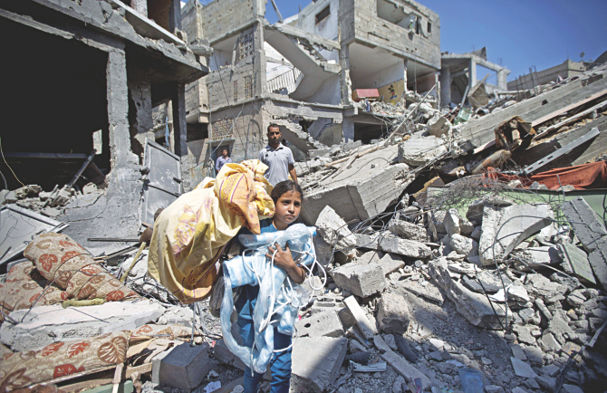 A Palestinian girl carries items she collected from the rubble of her home during a 72-hour ceasefire observed in the Gaza Strip yesterday.  Photo: AFP
