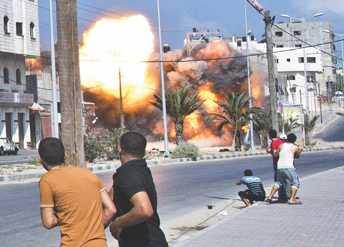 Palestinian men look on as a bomb from an Israeli air strike hits a house in Gaza City on August 23, 2014.  Photo: AFP