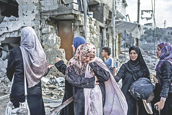 Palestinian women react amid the destruction in the district. Photo: AFP