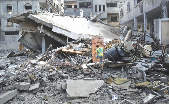 A Palestinian climbs through the rubble of a house after they were hit in Israeli air strikes in Gaza City yesterday. Violence reverberated across Gaza with four Palestinians killed in Israeli air strikes as Egypt proposed a new ceasefire that would open key crossings into the blockaded territory. Photo: AFP
