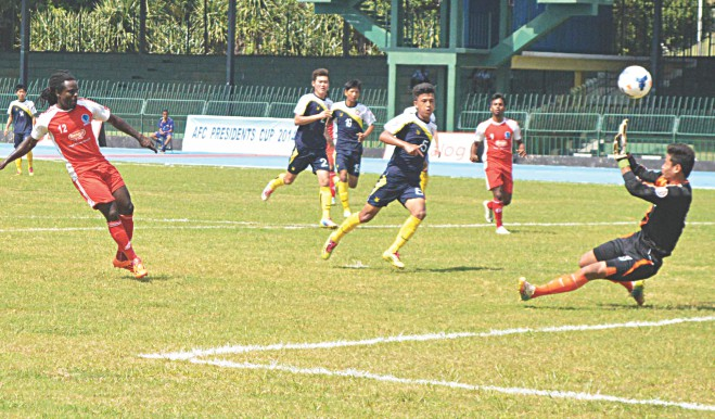 Sheikh Russel KC forward Pascal Millien (L) dinks one over the Ugyen Academy goalkeeper during their 4-0 victory in the Group A fixture of AFC President's Cup at the Sugathadasa Stadium in Colombo yesterday.  PHOTO: COURTESY