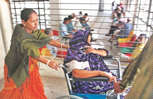 A relative pushing a patient in wheelchair to get services.  Photo: Anurup Kanti Das
