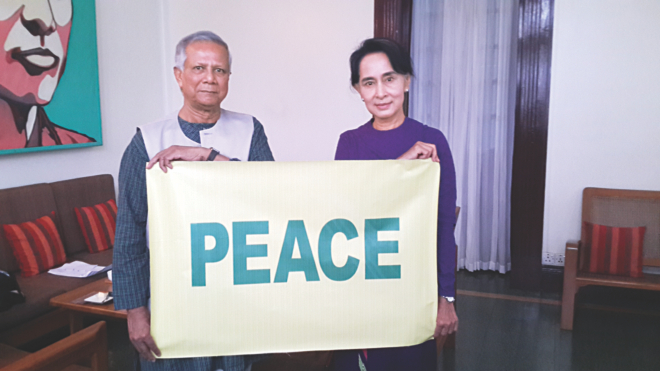 Nobel peace laureates Professor Muhammad Yunus and Aung San Suu Kyi hold up a peace sign together, as their message to the world during their meeting in Yangon, Myanmar on Saturday. Photo: Yunus Centre