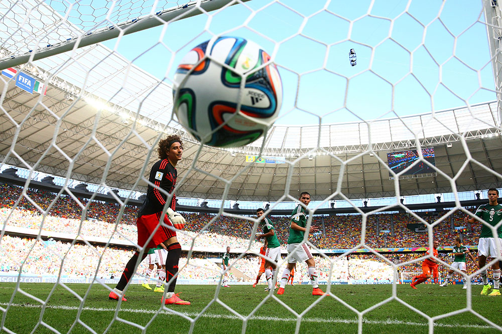 Wesley Sneijder of the Netherlands scores his team's first goal past Guillermo Ochoa of Mexico during the 2014 FIFA World Cup Brazil Round of 16 match between Netherlands and Mexico. Photo: Getty Images