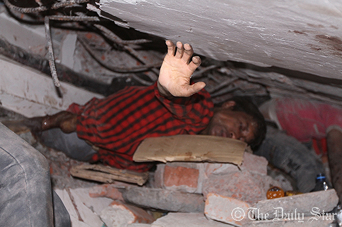 Trapped under tons of concrete and steel, a victim seeks help. He eventually died at the same place two days later. Photo: Star