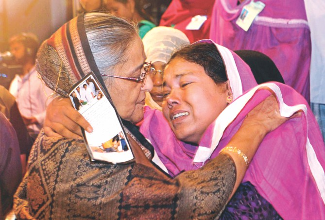 Prime Minister Sheikh Hasina consoles Layla Khatun, widow of police constable Hazrat Ali, who was killed while guarding a police post in Gaibandha during a spate of BNP-Jamaat violence last year. They met at the publication ceremony of a photo album Roktakto Bangladesh (Bloodstained Bangladesh) in the capital's Osmani Memorial Auditorium, containing photos of the barbaric activities, which left many civilians dead too. Photo: BSS