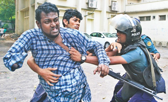 A physically challenged organiser of Gonojagoron Mancha struggles to free himself from policemen while another activist tries to help him at Shahbagh in the capital yesterday. Photo: Palash Khan