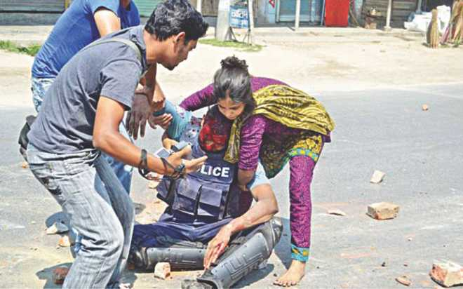 Jharna Begum rushes to  help a severely injured policeman.