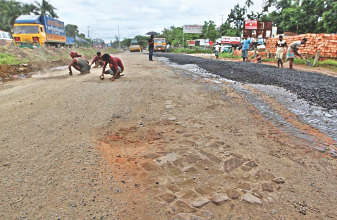 Workers mending the potholes at Sitakunda on Dhaka-Chittagong Highway yesterday.  Photo: Anurup Kanti Das/star