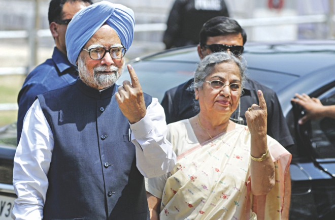 Indian Prime Minister Manmohan Singh holds up his ink-marked finger as he poses alongside his wife for a photograph after casting his ballot at a polling station in Guwahati, the capital of the northeastern state of Assam, yesterday.  Photo: AFP