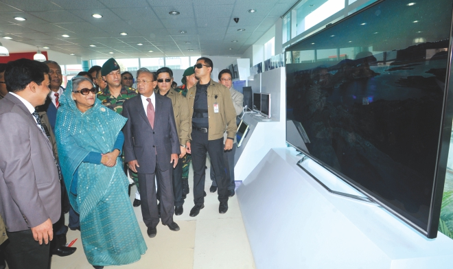 Prime Minister Sheikh Hasina looks at some large-screen TVs at a stall after inaugurating the International Trade Fair in the capital yesterday. Photo: BSS