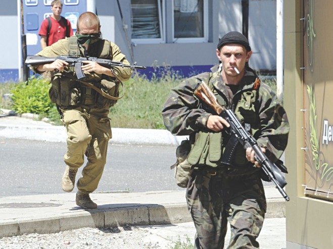 Armed pro-Russian separatists run during clashes between Ukrainian government troops and pro-Russian rebels that left at least three people dead in the eastern Ukrainian city of Donetsk yesterday. Photo: AFP