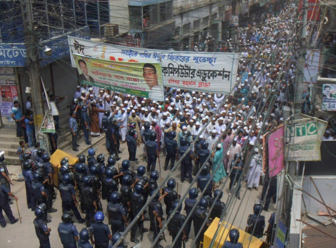 Police halt the procession of pro-Islamist Osamajik Karjokolap Protirodh Committee while going to besiege the Kandapara brothel in Tangail town yesterday. The processionists later held a sit-in blocking the busy road for hours. PHOTO: STAR