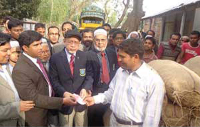 Prof Rafiqul Haque, vice chancellor of Bangladesh Agricultural University, Mymensingh, hands over money to a farmer as teachers, officers and employees of the university buy 500 maunds of potato from growers in Pirganj upazila under Rangpur district on the premises of Dumarimithipur Government Primary School in the upazila on Friday.  PHOTO: STAR