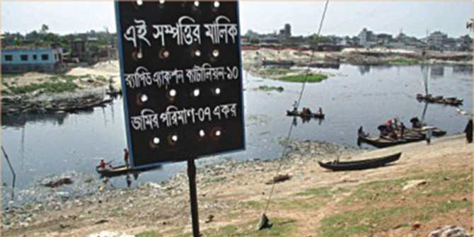 The Star file photo shows the Rapid Action Battalion-10 puts a sign on a channel of the Buriganga in Kamrangirchar, claiming seven acres of land there. Only a year ago, the BIWTA dredged this part of the river and is planning to set up a dock.