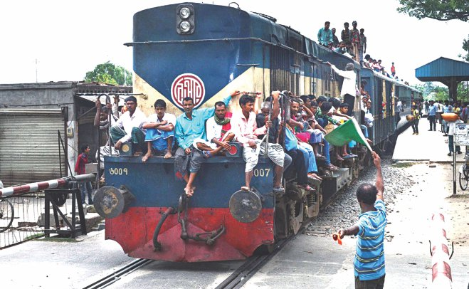 Failing to find room inside, people travel on the roof and the locomotive of a train at Court Railway Station in Rajshahi as there is no other option for them. Transport workers of the division have been on strike since Sunday.  Photo: Star