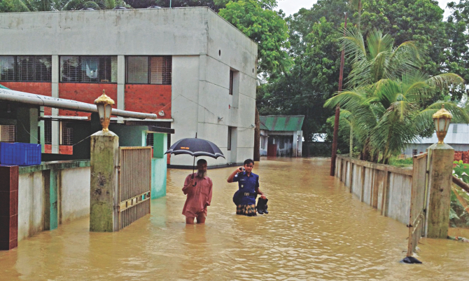 Phulgazi Police Station in Feni is flooded with waist-deep water rushing through breaches on an embankment. Photo: Star