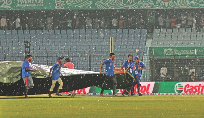 The covers are out as sudden rain lashes the Zohur Ahmed Chowdhury Stadium disrupting the ICC World T20 Super 10 match between New Zealand and England yesterday. PHOTOs: ANURUP KANTI DAS