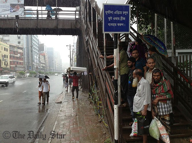 City dwellers take shelter under the shade of a foot-overbridge to dodge the heavy downpour that started from Wednesday evening. This STAR file photo was taken from capital's Kazi Narzul Islam Avenue.