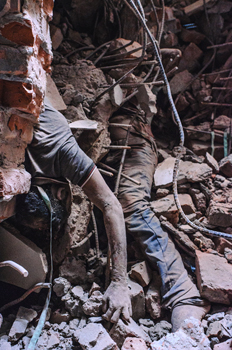 Corpses tangles in the rubble hang as rescuers make way into the collapsed structure. Photo Aninda Kabir Avik