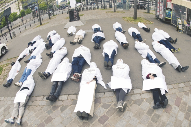 People wear funeral shrouds and lie on the ground in Paris yesterday as they take part in a protest marking the first anniversary of the Rana Plaza collapse in Bangladesh. Photo: AFP