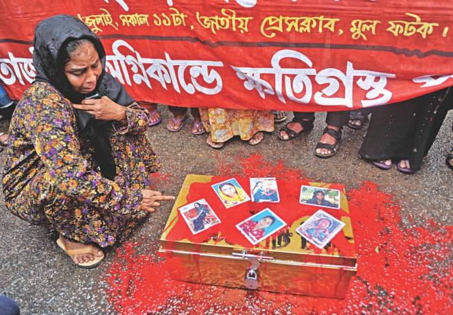 A sobbing Rokeya Begum sits before a trunk filled with fake money and covered with red paint symbolising the blood of missing workers of Tazreen Fashions whose photos are pasted on it during a human chain in front of Jatiya Press Club yesterday which demanded compensation from the prime minister's relief fund for the missing and the injured; her daughter Hena is one of the missing. Photo: Star