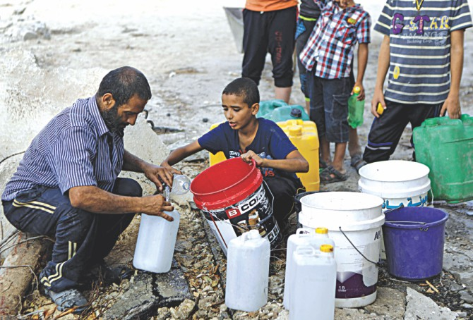 A Palestinian man and children fill containers with water from a broken pipe line. Photo: AFP
