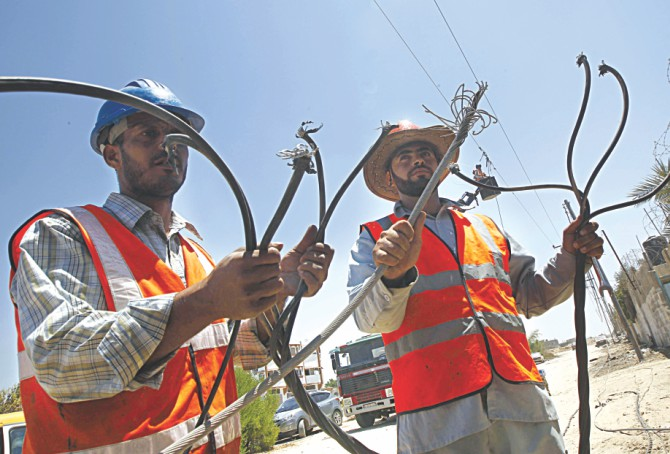 Palestinian electricity company workers inspect power lines destroyed by Israeli attacks. Photo: AFP