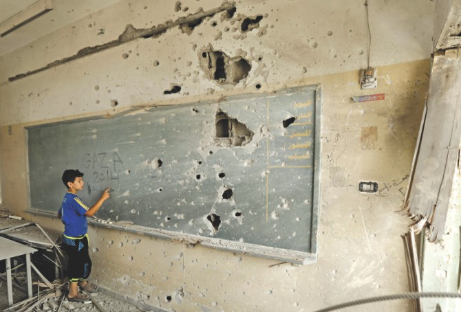 A Palestinian boy writes on a shrapnel riddled backboard at a school in Gaza City yesterday. Photo: AFP