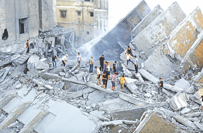 Palestinians inspect the remains of Al-Basha, a building that was destroyed by an Israeli air strike in Gaza City, yesterday. Photo: AFP
