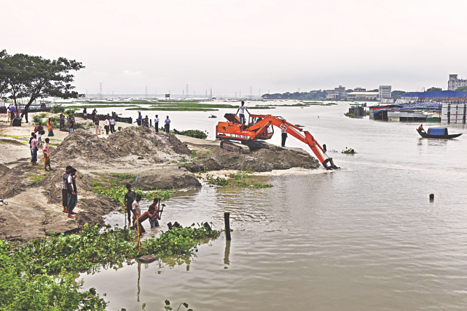 The BIWTA yesterday removes the soil a grabber had dumped in the Turag at Dhour near Ashulia to occupy the river. Photo: Rashed Shumon