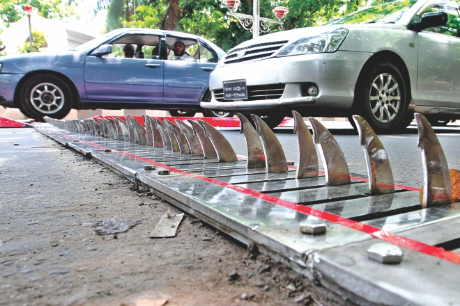 The retractable spike strip installed on Hare Road in Dhaka yesterday to prevent motorists from driving on the wrong side of the road.  Photo: Anisur Rahman