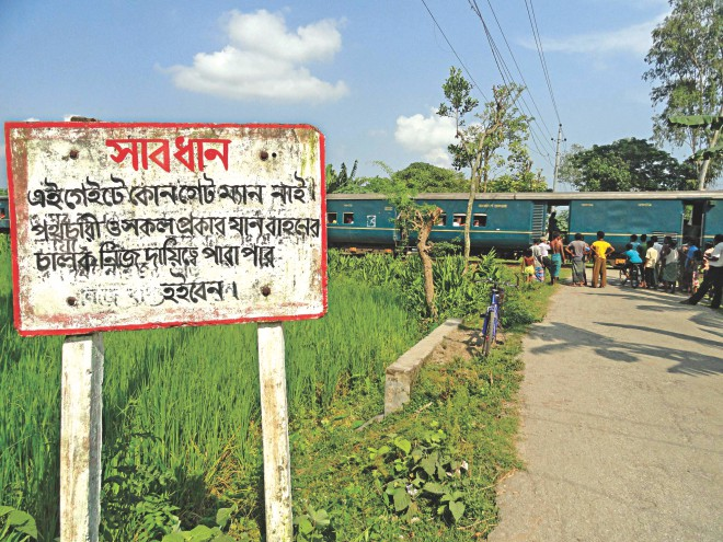 The road was built by the government, the rail tracks too. But for any accident at this unprotected level crossing, it is the pedestrians or drivers who will be held responsible. Conveying a warning is all that the authorities have done. This level crossing, on Jail Road in Lalmonirhat town, has neither a gate nor a guard. Photo: Star