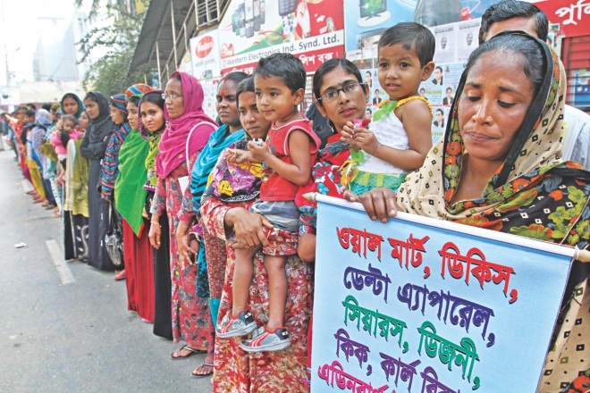 Garment workers form a human chain in front of the National Press Club in Dhaka yesterday to demand arrest of the owner of Tazreen Fashions where a fire killed 112 people last year. The workers also sought compensation from western retailers who sourced garments from Tazreen. Photo: star