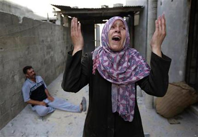 As her brother-in-law Mazen Keferna, background left, weeps, Palestinian Manal Keferna, 30, right, cries upon her return to the family house, destroyed by Israeli strikes in Beit Hanoun, northern Gaza Strip,  July 26. Photo: AP